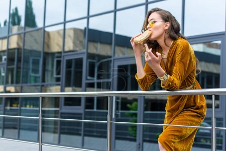woman in fashionable dress eating french hot dog and showing middle finger on street