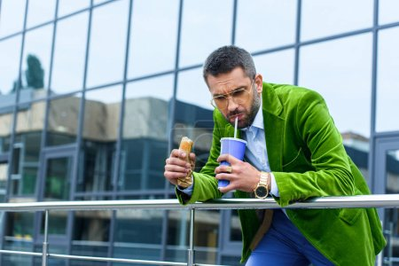 portrait of man in green velvet jacket with french hot dog drinking soda drink on street