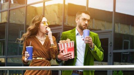 Photo pour Portrait de couple à la mode en vêtements de velours avec boissons gazeuses mangeant des jambes de poulet frit tout en marchant dans la rue - image libre de droit