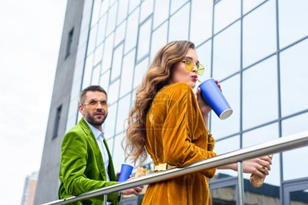 side view of stylish couple in velvet clothing with soda drinks and french hot dogs on street