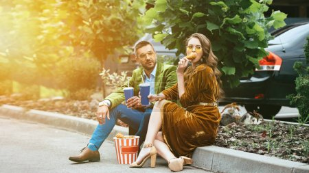 fashionable couple in velvet clothing with drinks eating fried chicken legs on street