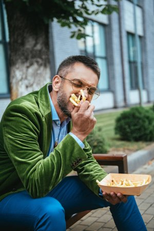 portrait of man in green velvet jacket eating french fries while sitting on bench on street