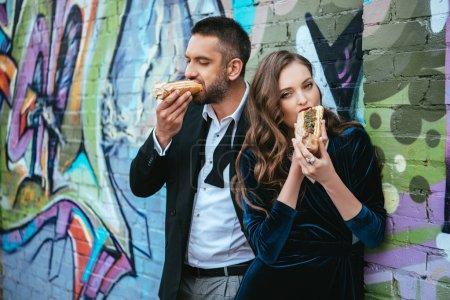Photo pour Portrait de couple dans des vêtements de luxe manger des hot-dogs près de mur de graffitis sur rue - image libre de droit