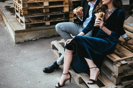 cropped shot of couple in luxury clothing with hot dogs sitting on wooden pallet on street