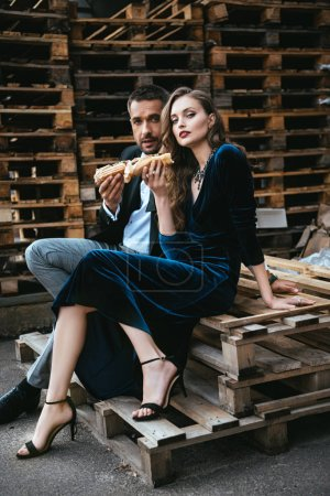 side view of couple in luxury clothing with hot dogs sitting on wooden pallet on street