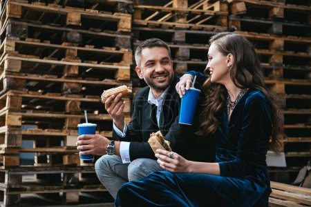 side view of smiling couple in luxury clothing with hot dogs and soda drinks sitting on wooden pallet on street