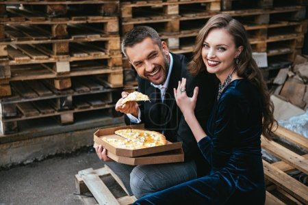 side view of happy stylish couple with italian cheese pizza resting on street