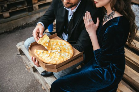 partial view of couple in stylish clothing with cheese pizza in box on street