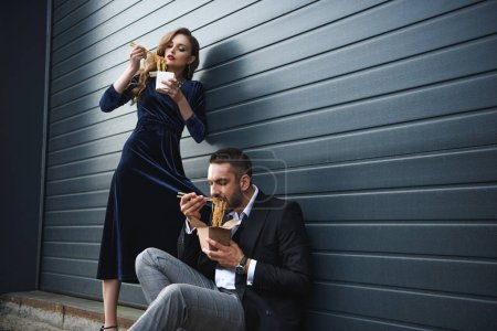 couple in fashionable clothing eating asian takeaway food on street