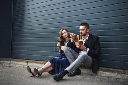 Photo pour Couple dans des vêtements à la mode avec des aliments à emporter asiatiques assis sur la rue - image libre de droit