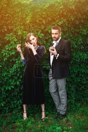 fashionable couple with chocolate doughnuts with green foliage behind