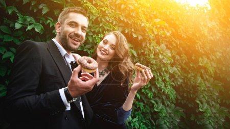 Photo pour Portrait du couple à la mode avec des beignets au chocolat avec un feuillage vert derrière de sourire - image libre de droit