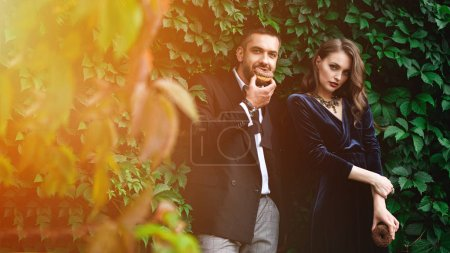 portrait of fashionable couple with chocolate doughnuts with green foliage behind