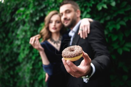 selective focus of fashionable couple with chocolate doughnuts with green foliage behind