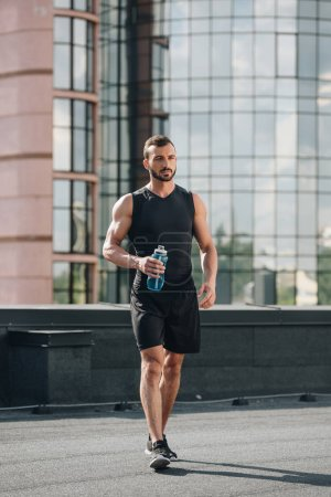 handsome sportsman walking with sport bottle of water on roof