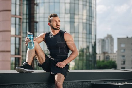 Photo for Handsome sportsman resting and holding sport bottle of water on roof - Royalty Free Image