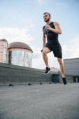 low angle view of handsome sportsman running and listening music with smartphone on roof
