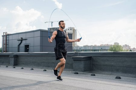 Photo for Handsome sportsman training with jumping rope on roof - Royalty Free Image