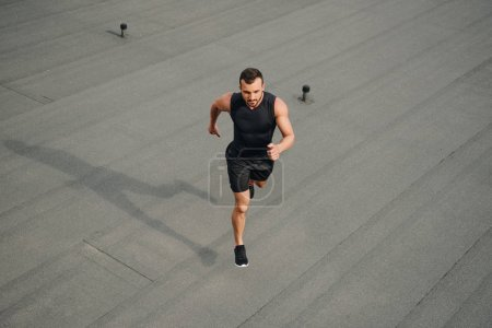 high angle view of handsome sportsman running on roof