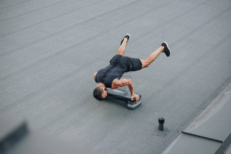 Photo for High angle view of sportsman training with step platform and standing on hands on roof - Royalty Free Image