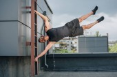 handsome strong sportsman training with ladder on roof