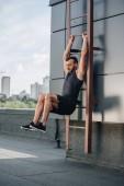 handsome sportsman training on ladder on roof