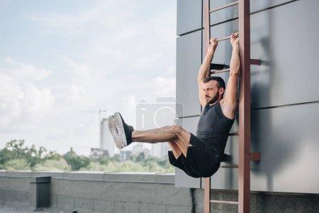 Handsome sportsman doing leg raises on ladder on roof