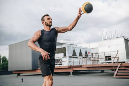 handsome sportsman training with medicine ball on roof