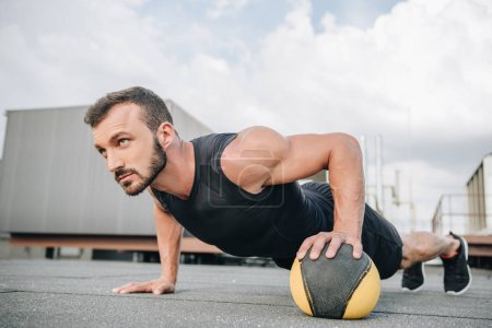 handsome sportsman doing push ups with medicine ball on roof
