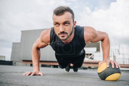 handsome muscular sportsman doing push ups with medicine ball on roof