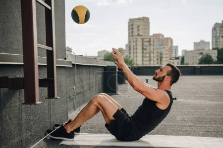 side view of handsome sportsman doing sit ups with medicine ball on yoga mat on roof