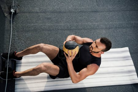 high angle view of handsome sportsman doing sit ups with medicine ball on yoga mat on roof