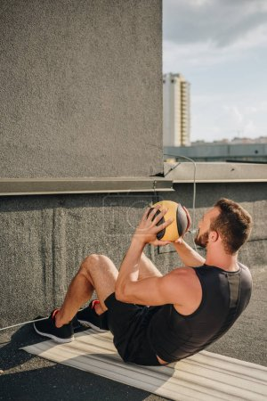 sportsman doing sit ups with medicine ball on yoga mat on roof