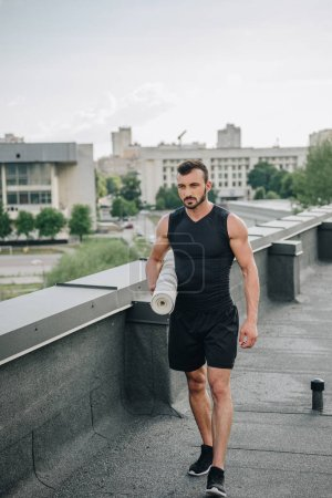 handsome sportsman walking with yoga mat on roof