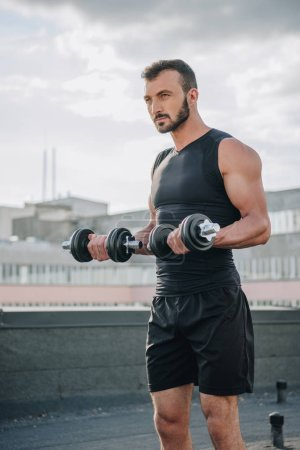 handsome sportsman training with dumbbells on roof