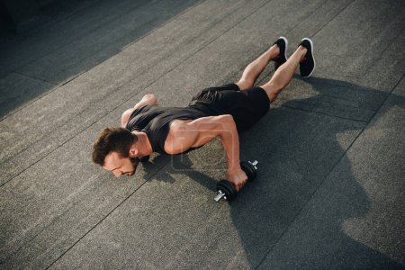Photo for High angle view of handsome sportsman doing push ups with dumbbells on roof - Royalty Free Image