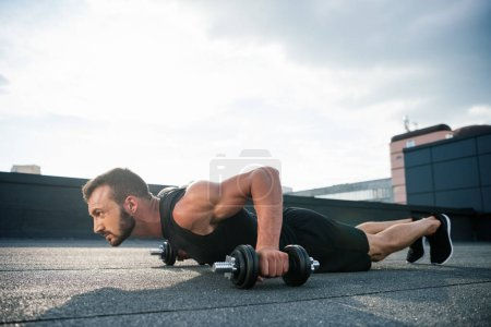 side view of handsome sportsman doing push ups with dumbbells on roof
