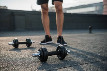 Photo for Cropped image of sportsman standing near dumbbells on roof - Royalty Free Image