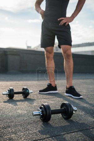 cropped image of man standing near dumbbells on roof