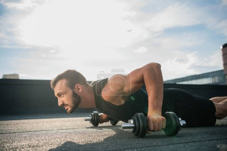 Photo for Side view of handsome sportsman doing plank on dumbbells on roof - Royalty Free Image