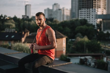 handsome sportsman with jumping rope on neck sitting on roof and looking at camera