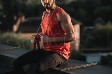 cropped image of sportsman with jumping rope on neck sitting on roof