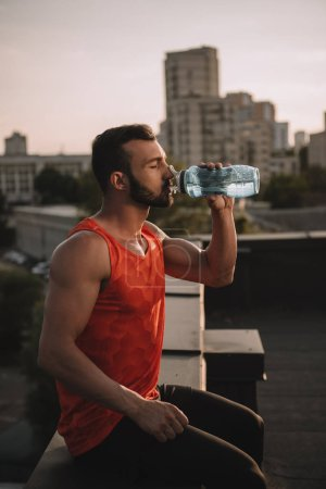 Photo for Side view of handsome sportsman drinking water on roof - Royalty Free Image