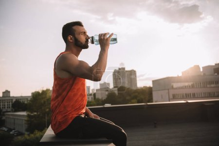 side view of handsome sportsman drinking water from sport bottle on roof