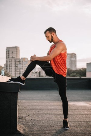 side view of handsome sportsman stretching legs on roof