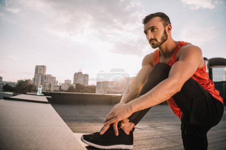 handsome sportsman stretching legs on roof during sunset