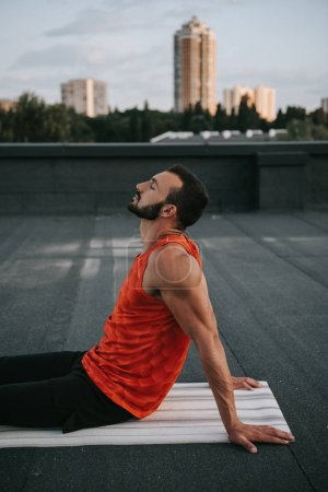 side view of handsome man sitting on yoga mat with closed eyes on roof