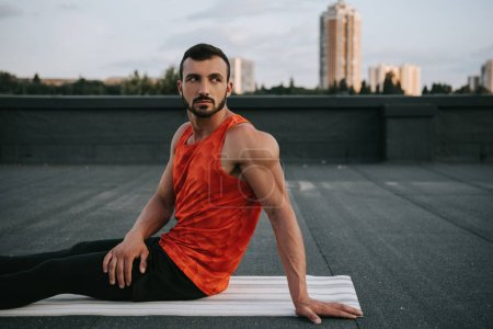 handsome man resting on yoga mat after practicing yoga on roof