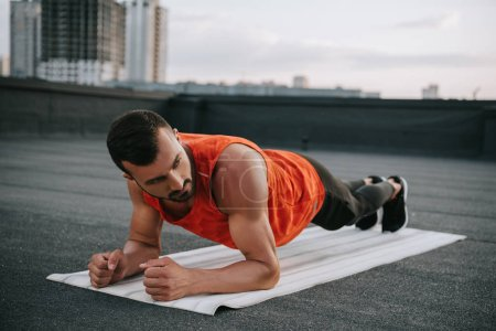handsome sportsman doing plank on yoga mat on roof