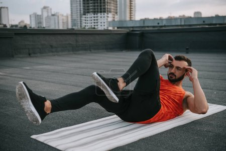 handsome sportsman doing sit ups on yoga mat on roof